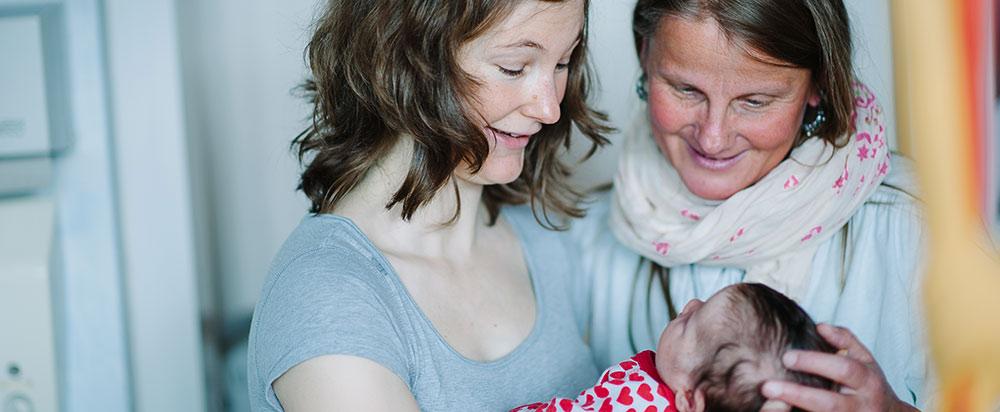 Mutter und Hebamme mit Kind